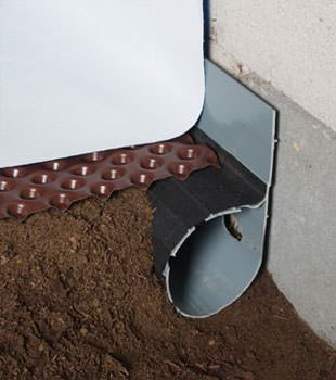 Closeup of a crawl space drainage system installed in Indian